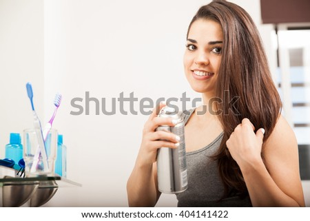Portrait of a beautiful young Latin brunette styling her hair with a bottle of spray and smiling