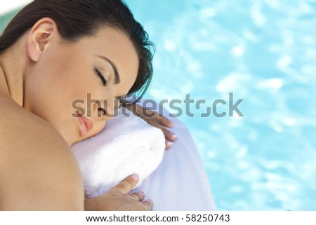 Portrait of a beautiful young Latina Hispanic woman eyes closed laying down and relaxing by a swimming pool at a health spa