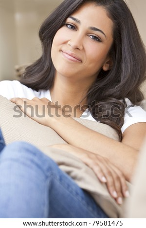 Portrait of a beautiful young Latina Hispanic woman or girl sitting at home on a sofa holding a cushion smiling and happy