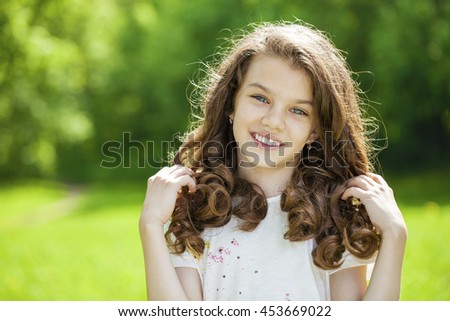 Portrait of a beautiful young little girl on the background of summer park - stock photo