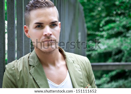 Portrait of  a beautiful young man outdoors against iron gate