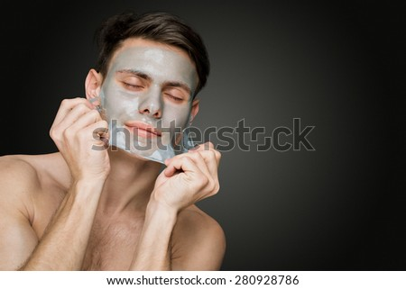Portrait of a beautiful young man peeling off a facial mask, face and body skin care retreat. - stock photo