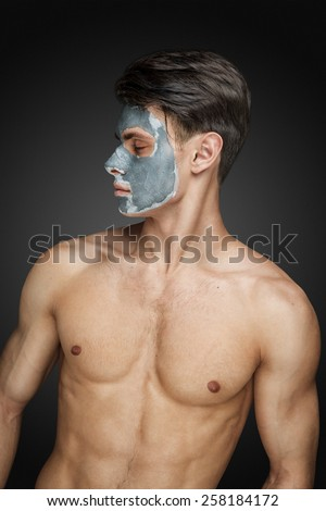 Portrait of a beautiful young man with a facial mud clay mask, face and body skin care treatment. - stock photo