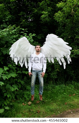 portrait of a beautiful young man with big angel's wings