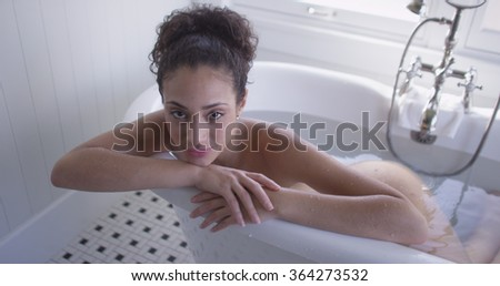 Portrait of a beautiful young mixed ethnic woman in a bathtub.