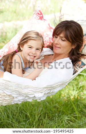 Portrait of a beautiful young mother and daughter laying and relaxing together on a hammock during a sunny summer day on holiday home garden. Family relaxing outdoors, healthy and wellness lifestyle.