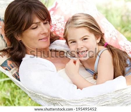 Portrait of a beautiful young mother and daughter laying down relaxing together on a hammock during a sunny summer day on holiday home garden. Family relaxing outdoors, healthy and wellness lifestyle. - stock photo