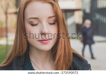 Portrait of a beautiful young redhead girl posing in the city streets