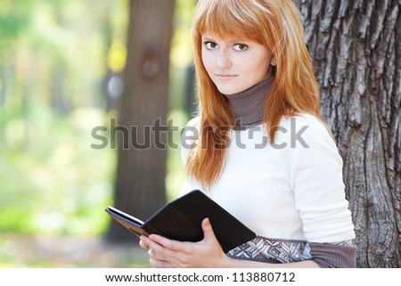 portrait of a beautiful young redhead teenager woman reading a book - stock photo