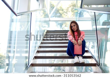 Portrait of a beautiful young teenager girl holding a notepad while sitting on the steps in university hallway, intelligent caucasian college student resting after a training classes at campus  - stock photo
