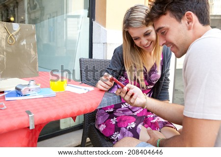 Portrait of a beautiful young tourist couple sitting together at a cafe terrace with refreshments and shopping, visiting a destination city and using smartphone outdoors. Technology travel lifestyle. - stock photo