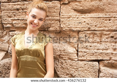 Portrait of a beautiful young tourist woman leaning on a golden aged textured stone wall, smiling and looking at camera with friendly expression, sunny outdoors. Youthful face, recreation lifestyle. - stock photo