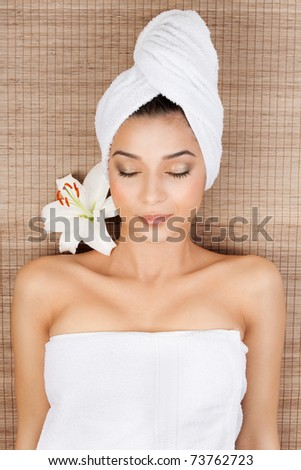 portrait of a beautiful, young woman, at a spa, lying on her back on a bamboo mat, with a towel in her head, smiling, with a lily near her head and her eyes closed. - stock photo