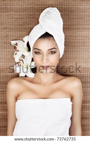 portrait of a beautiful, young woman, at a spa, lying on her back on a bamboo mat, with a towel in her head, smiling, with two lilies near her head. - stock photo