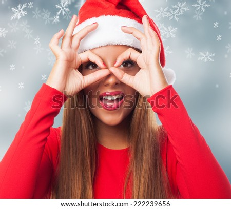 portrait of a beautiful young woman at Christmas doing the glasses gesture - stock photo