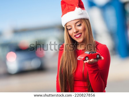 portrait of a beautiful young woman at Christmas holding a toy car