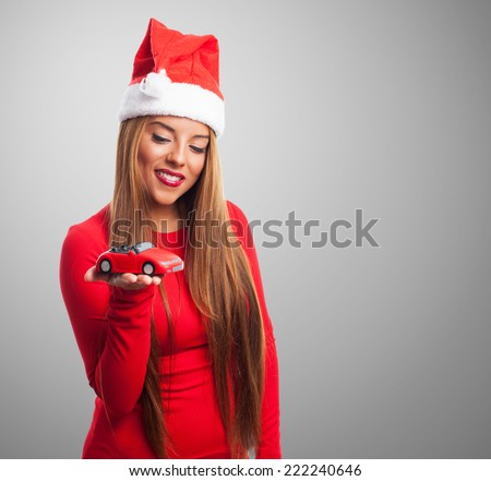 portrait of a beautiful young woman at Christmas holding a toy car - stock photo