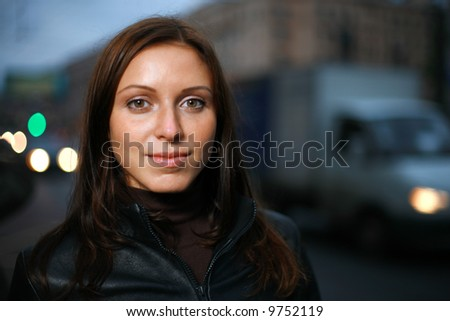 Portrait of a beautiful young woman at dusk. Shallow DOF, focus on eyes. - stock photo