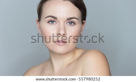 Portrait of a beautiful young woman. Beautiful female face on a gray background.