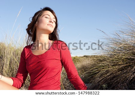 Portrait of a beautiful young woman breathing fresh air while sitting on a beach sand dunes with her eyes closed, leaning her head back and enjoying the breeze on vacation. - stock photo