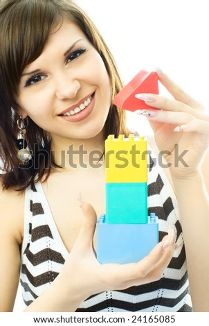 portrait of a beautiful young woman building a toy house - stock photo