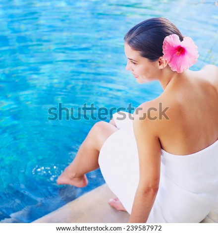 Portrait of a beautiful young woman by swimming pool - stock photo