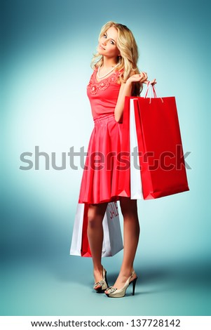 Portrait of a beautiful young woman carrying shopping bags. - stock photo