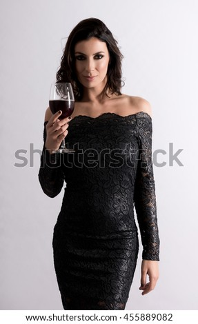 Portrait of a beautiful young woman enjoying a glass of wine while wearing a nice black dress in the studio. - stock photo