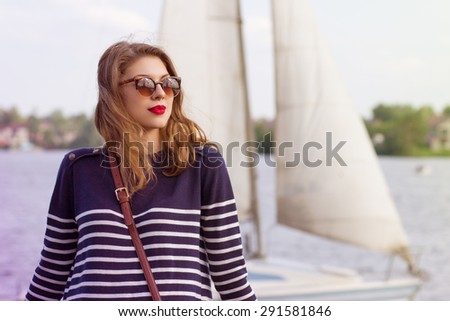 Portrait of a beautiful young woman floating on a yacht. - stock photo