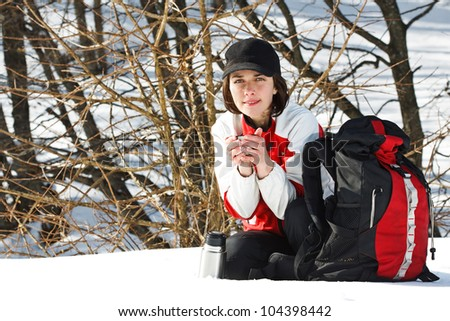 Portrait of a beautiful young woman going on trip with sporty clothes, cap, rucksack, sitting next to her rucksack, smiling, holding a cup of hot drink in her hands - stock photo