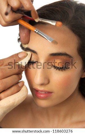 Portrait of a beautiful young woman having make up removed from eye