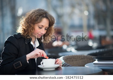 portrait of a beautiful young woman having tea in a cafe terrace