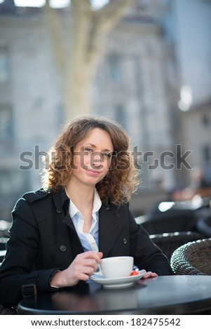 portrait of a beautiful young woman having tea in a cafe terrace - stock photo