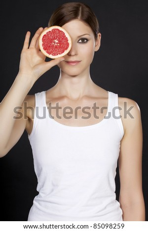 Portrait of a beautiful young woman holding a half grapefruit in front of her face