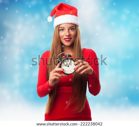portrait of a beautiful young woman holding an alarm clock at Christmas