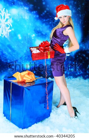 Portrait of a beautiful young woman holding present over sky of stars and snow.