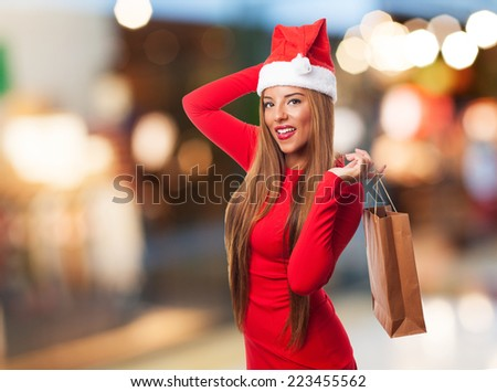 portrait of a beautiful young woman holding shopping bags and wearing a Christmas hat