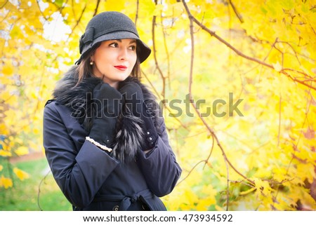 Portrait of a beautiful young woman in a black coat and hat on a background of yellow autumn landscape