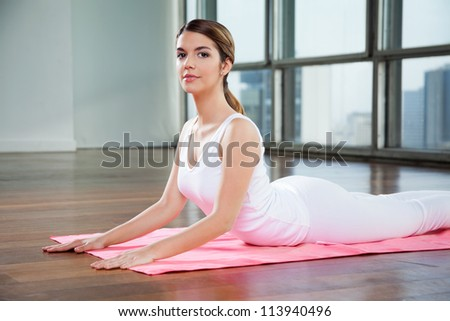 Portrait of a beautiful young woman in a cobra pose on mat - stock photo