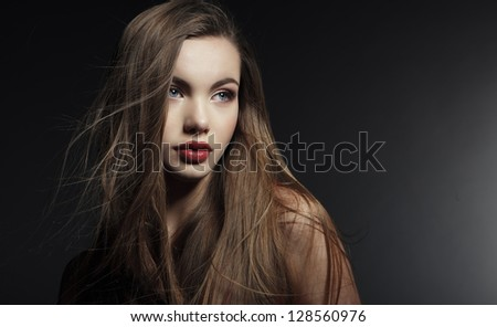 Portrait of a beautiful young woman in a red dress on a dark background. - stock photo