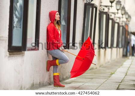 Portrait of a beautiful young woman in a red hooded raincoat leaning on the wall and looking for the rain to stop. - stock photo