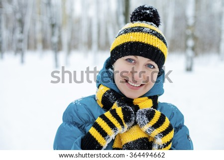 Portrait of a beautiful young woman in a turquoise feather bed and a knitted cap on a background of a winter park - stock photo