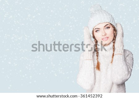 Portrait of a beautiful young woman in a warm cozy knitted dress, she is dressed in a light head cap and mittens.Woman in winter.WARM knit women's clothes