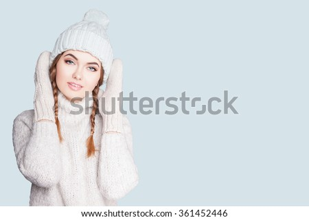 Portrait of a beautiful young woman in a warm cozy knitted dress, she is dressed in a light head cap and mittens.Woman in sweater and mittens. WARM knit women's clothes
