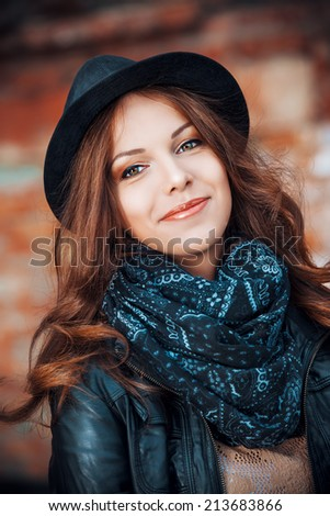 Portrait of a beautiful young woman in black leather jacket and a hat posing over brick wall.