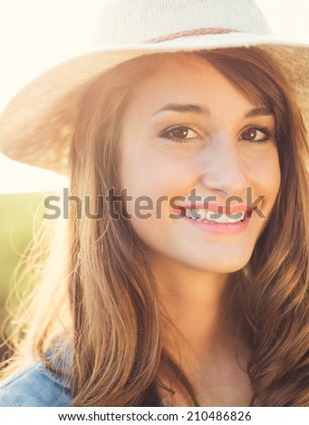 Portrait of a beautiful young woman in hat outside, bright warm sunny color tones