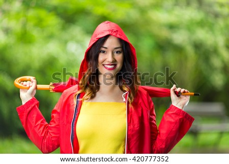 Portrait of a beautiful young woman in hooded red raincoat holding red umbrella. She is looking at camera and smiling while walking in the park on a rainy day.  - stock photo