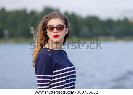 Portrait of a beautiful young woman in sunglasses outdoors. - stock photo