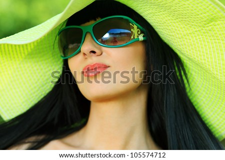 Portrait of a beautiful young woman in sunglasses posing outdoor. - stock photo