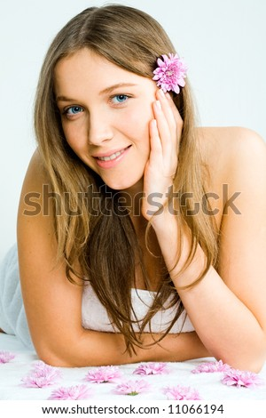 Portrait of a beautiful young woman in towel lying on the massage table before enjoying spa procedures - stock photo